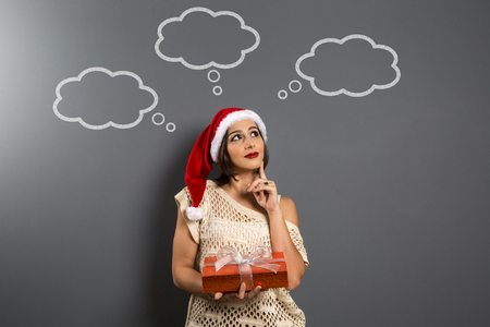 santa clause hat: christmas girl look up empty copy space hold gift box present, young happy smile woman wear Santa Clause hat, attractive new year party girl, over blackboard with empty ballons Stock Photo