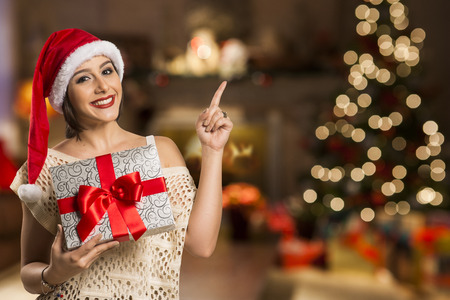 gesturing: woman happy smile point finger showing side empty copy space, young excited girl wear santa hat, advertisement product over christmas background