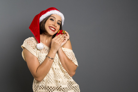 envisioning: Christmas gift. Smiling beautiful woman in red hat and scarf envisioning with closed eyes what is in the gift box, over grey background Stock Photo