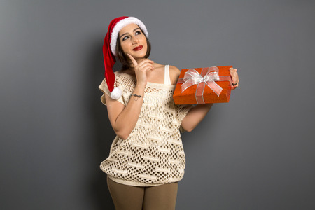 santa clause hat: christmas girl look up empty copy space hold gift box present, young happy smile woman wear Santa Clause hat, attractive new year party girl, over grey background Stock Photo