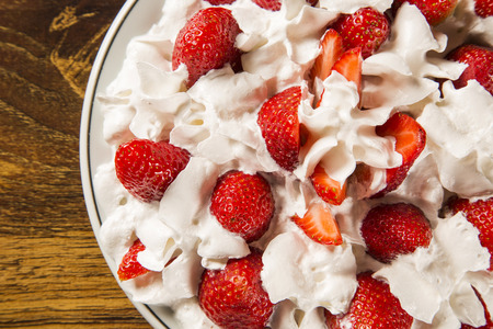 chantilly: Strawberry with chantilly cream in a dish on a wooden table Stock Photo