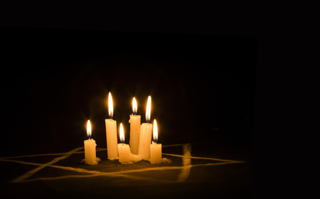 heroism: Six burning candles and the Star of David against a black background, text Yom Hashoah, We will never forget, the Jewish Holocaust and Heroism Remembrance Day
