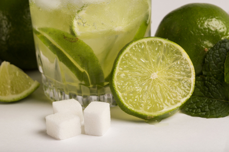 lemon wedge: Caipirinha - brazilians national cocktail made with cachaca, sugar and lemon or lime, isolated on white background Stock Photo