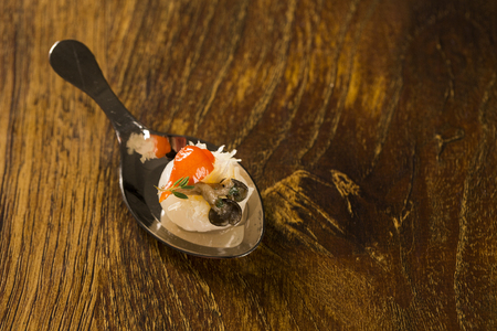Lychee with sour cream, parmesan cheese, shimeji, red pepper and thyme in a spoon. Taste gastronomy finger food