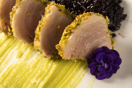 crust: Tuna with pistachio crust, black rice and avocado puree Stock Photo