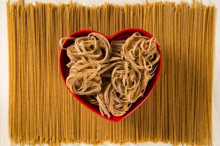 Wholemeal Pasta. Integral tagliatelle  into a heart bowl over a wooden table top view Stock Photo