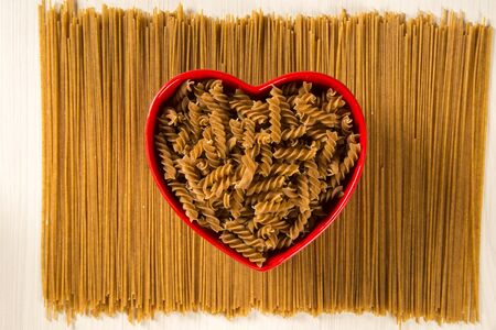 Wholemeal Pasta. Integral fusilli into a heart bowl over a wooden table top view Stock Photo