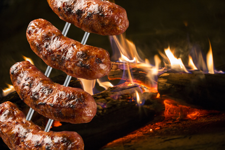 Saucisses à la broche barbecue avec des flammes