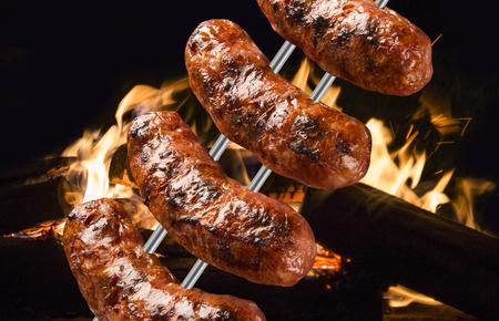 Saucisses sur le barbecue cracher avec des flammes