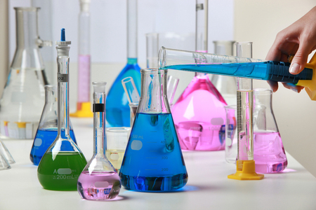 Composition of laboratory material with colored liquids in realistic glass pots chemical test for soy and corn.