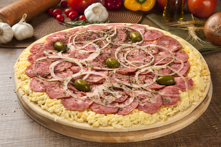 Raw pizza with pepperoni on wooden background