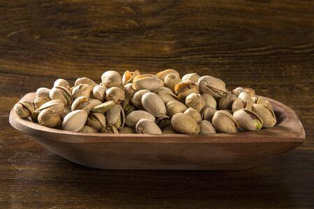 pistaches dans un bol en bois avec fond en bois. Banque d'images