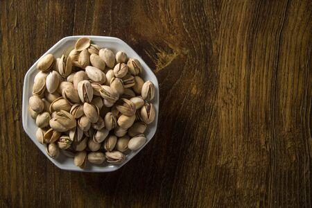 pistaches dans un bol blanc avec fond de bois.