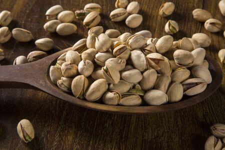pistaches dans une cuillère en bois sur fond de bois