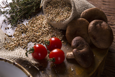 Rustic wood with fresh wheat, mushrooms and tomatoes Stock Photo