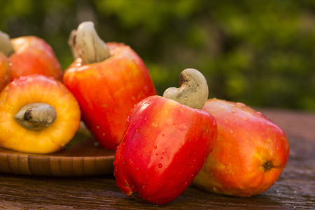 Some cashew fruit over a wooden surface.