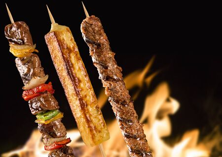 grill: Assorted steak skewers on a fire background.