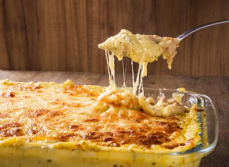 ハムとパルメザン チーズたっぷりポテト グラタン、南チロルからクリームとおいしい燻製ベーコンは、新鮮な木製テーブルにオーブンから提供して