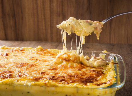 Hearty potato gratin with ham and parmesan cheese, cream and delicious cured bacon from South Tyrol freshly served from the oven on a wooden table