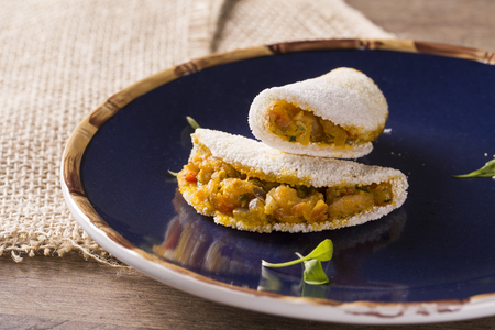Delicious Tapioca, a brazilian snack made with cassava flour and shrimp, manioc on a blue plate