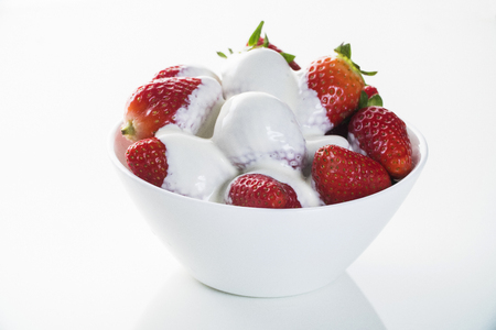 Strawberry with chantilly in white bowl on white background