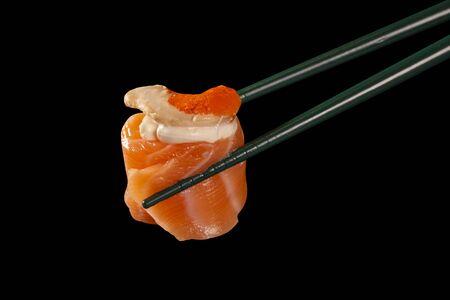 Hashi hold sushi and rolls isolated over black background. Standard-Bild