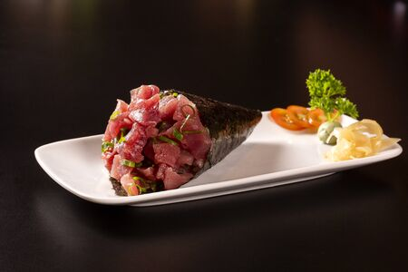 Tuna fish temaki sushi into a white plate in black background.