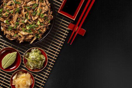 shimeji mushrooms in iron pan with ginger, wasabi and sunomono in a black background.Top View Standard-Bild