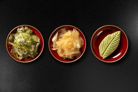 Sunomono, ginger and wasabi isolated on black background. top view