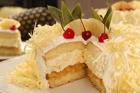 Macro close up of appetizing white chocolate cake with pineapple and cherry with out of focus cake in background