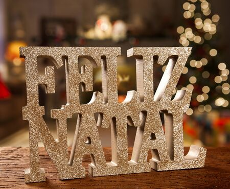 Merry Christmas greeting message on wooden background. Merry Christmas written in Portuguese. Feliz natal. Standard-Bild