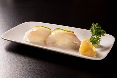 Nigiri Shiromi sushi with white fish on black background.