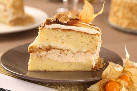 Macro close up of appetizing slice of white chocolate cake with walnuts and Physalis with out of focus cake in background