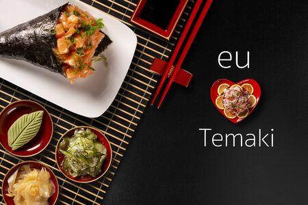 Salmon temaki sushi on white plate in black background. Written I love Temaki in portuguese. Top view