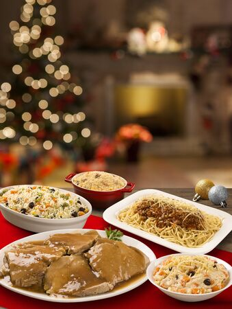 table with meat, bolognaise pasta, rice colorful and mayonnaise with Christmas background