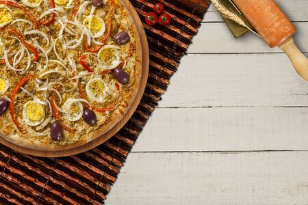 hot homemade brazilian pizza on wood table, top view. Copy space