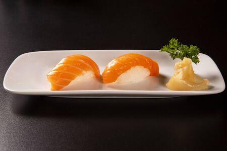 Sake - nigiri sushi with raw salmon on black background.