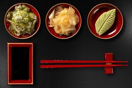 Sunomono, ginger, wasabi, hashi and shoyu isolated on black background. top view