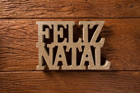 Merry Christmas greeting message on wooden background. Merry Christmas written in Portuguese. Feliz natal. Stock Photo