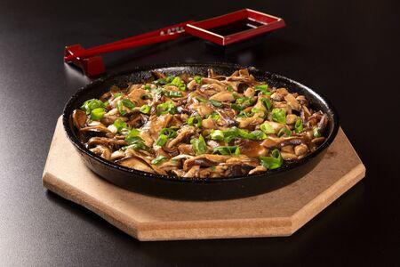 Shitake mushrooms in iron pan in a black background