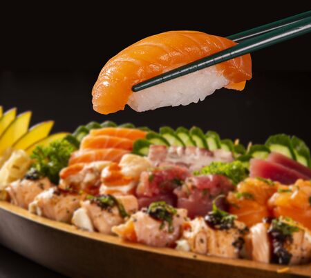close up salmon nigiri in hashi with Japanese food combo defocused in black background.