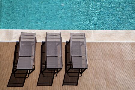 empty poolside deck chairs with beautiful blue swimming pool Standard-Bild