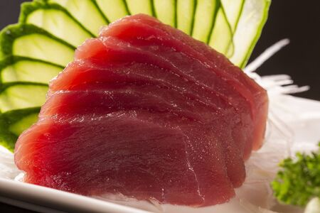 sashimi with tuna in a white plate. On a black background