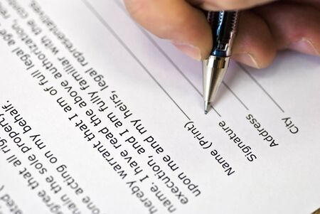 Human hand with pen makes signature