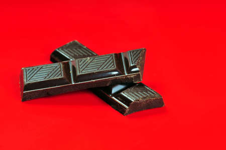Chocolate pieces on red background Stock Photo - 4296819