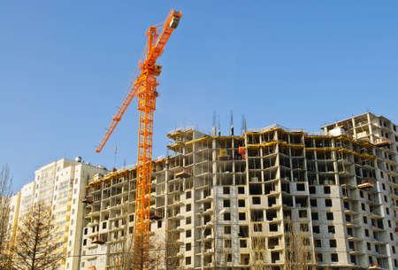 erect: construction crane and building over blue sky