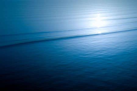 太陽光の反射と穏やかな海の水の表面 写真素材