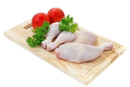 Raw chicken legs with vegetables and spices on the chopping board