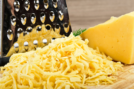 grated cheese on wooden board Archivio Fotografico