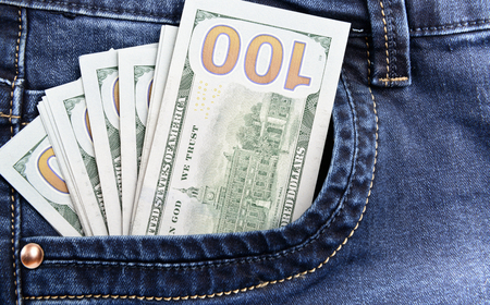 100 dollar bills money in pocket of blue jeans